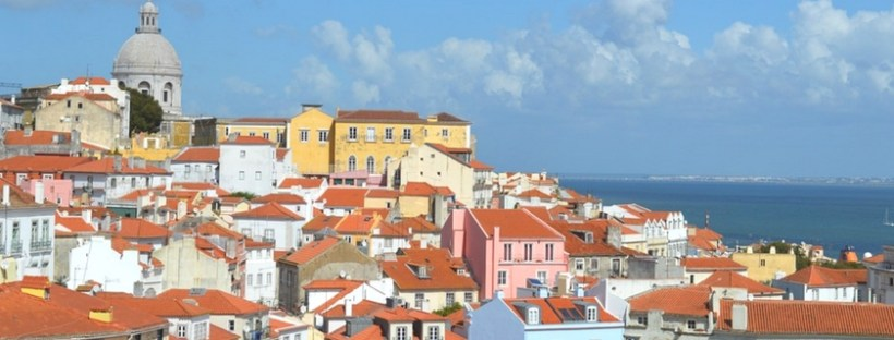 Lisbon cityscape with colorful buildings, clouds and water in the background
