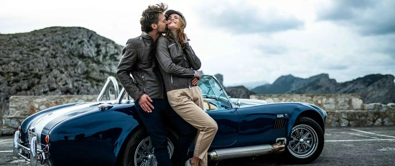 Panoramabild auf dem ein Paar in den Heinz Bauer Lederjacken Tempelhof und Topgear die Zweisamkeit in den Bergen genießt und sich an ein getuntes Classic Cabriolet lehnt.