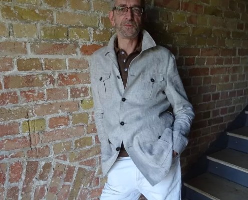 CM lehnt an einer Wand im ARTmax und präsentiert dabei lässig das neue Field Jacket nach Maß von Rebmann aus Leinenstoff - hier ohne Gürtel