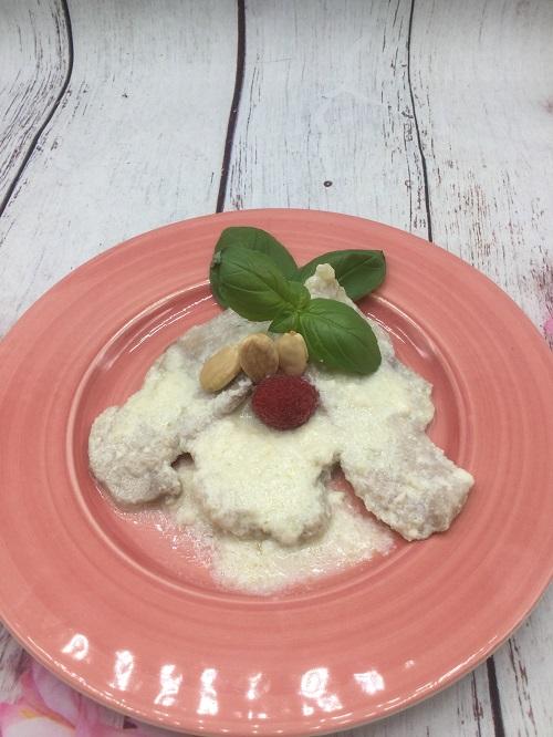 Plato terminado de lomo con salsa de almendras y leche. Se ve la carne la salsa y adornado con unas almendras, una hoja de albahaca y una frambuesa.