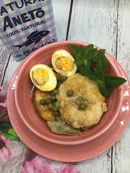 Plato de merluza guisada con huevo y verduras y al lado tetrabrick de Caldo Aneto de Pescado