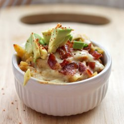 close up shot of macaroni and cheese topped with bacon bits and avocado served in a white ramekin