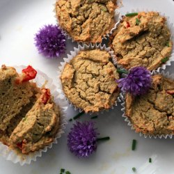 overhead shot of five muffins in white wrappers garnished with purple chive blossoms