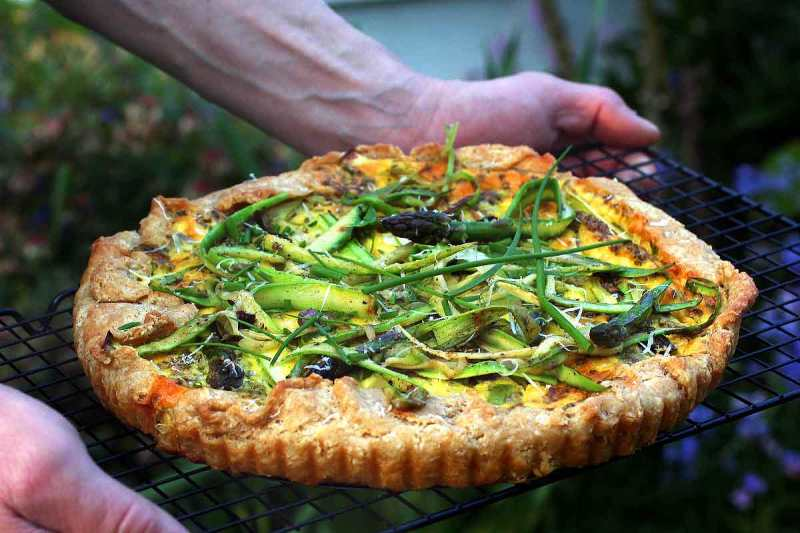 Asparagus Tart (with chives) being held on a black cooling rack outside in the garden