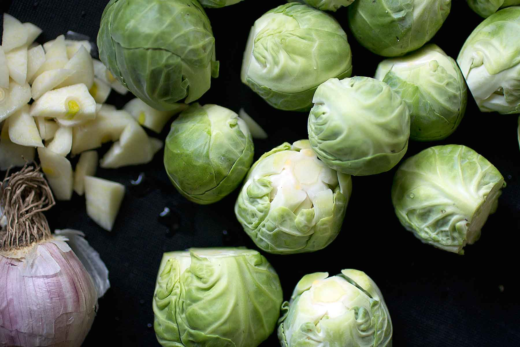 Prepping brussel sprouts and garlic for pan fried brussel sprouts