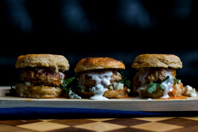side view of Three Buffalo Biscuit Sliders with buttermilk blue cheese dressing on a light wooden cutting board and wooden chess board with a blue napkin