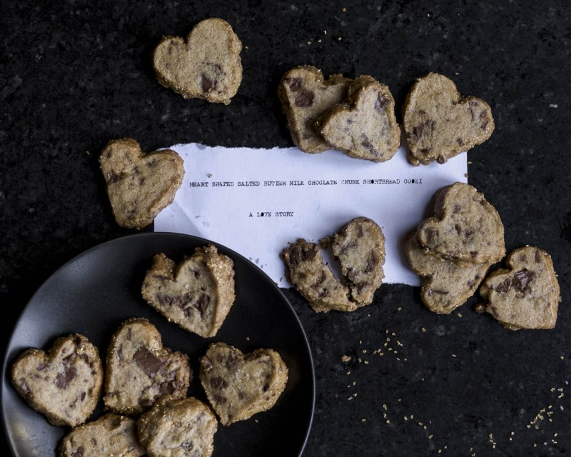 overhead shot of heart shaped, salted butter, milk chocolate chunk, shortbread cookies on a black plate with a typewritten description