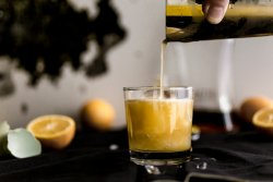 pouring a meyer lemon amaretto sour from silver shaker into clear lowball glass