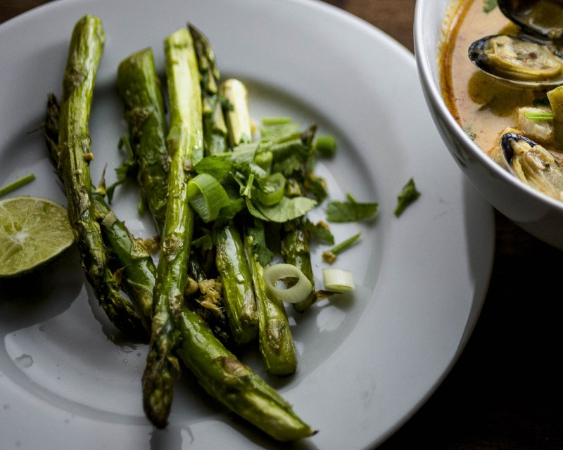 close up of garlic ginger asparagus on a small white plate with just a bit of curry clam chowder in a white bowl showing
