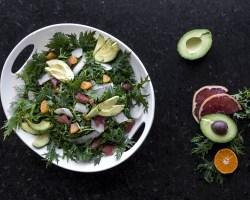 Overhead shot of white platter filled with dark green Mizuna Citrus Salad w/ avocado and jicama