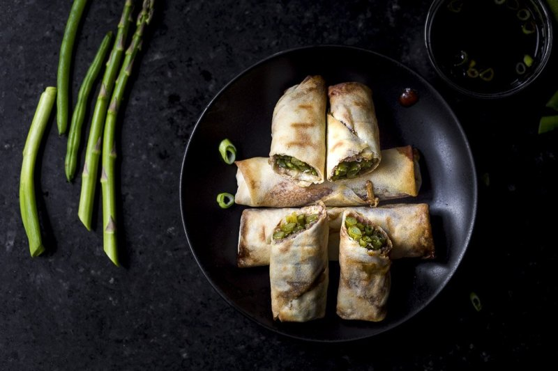 overhead shot of crispy baked vegetable egg rolls with asparagus, green beans, scallions, cream cheese, and (optional) prosciutto on a black plate