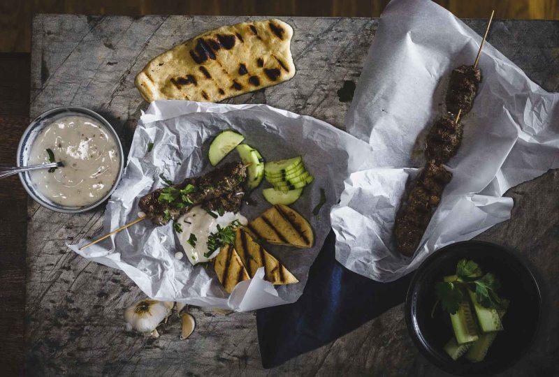 Kofta-esque: ground beef kebabs with yogurt dipping sauce overhead shot with flatbread and cucumber