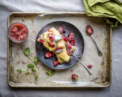 Sheet Pan Swedish Pancakes with fresh strawberries and lime from above on a black plate with fresh mint