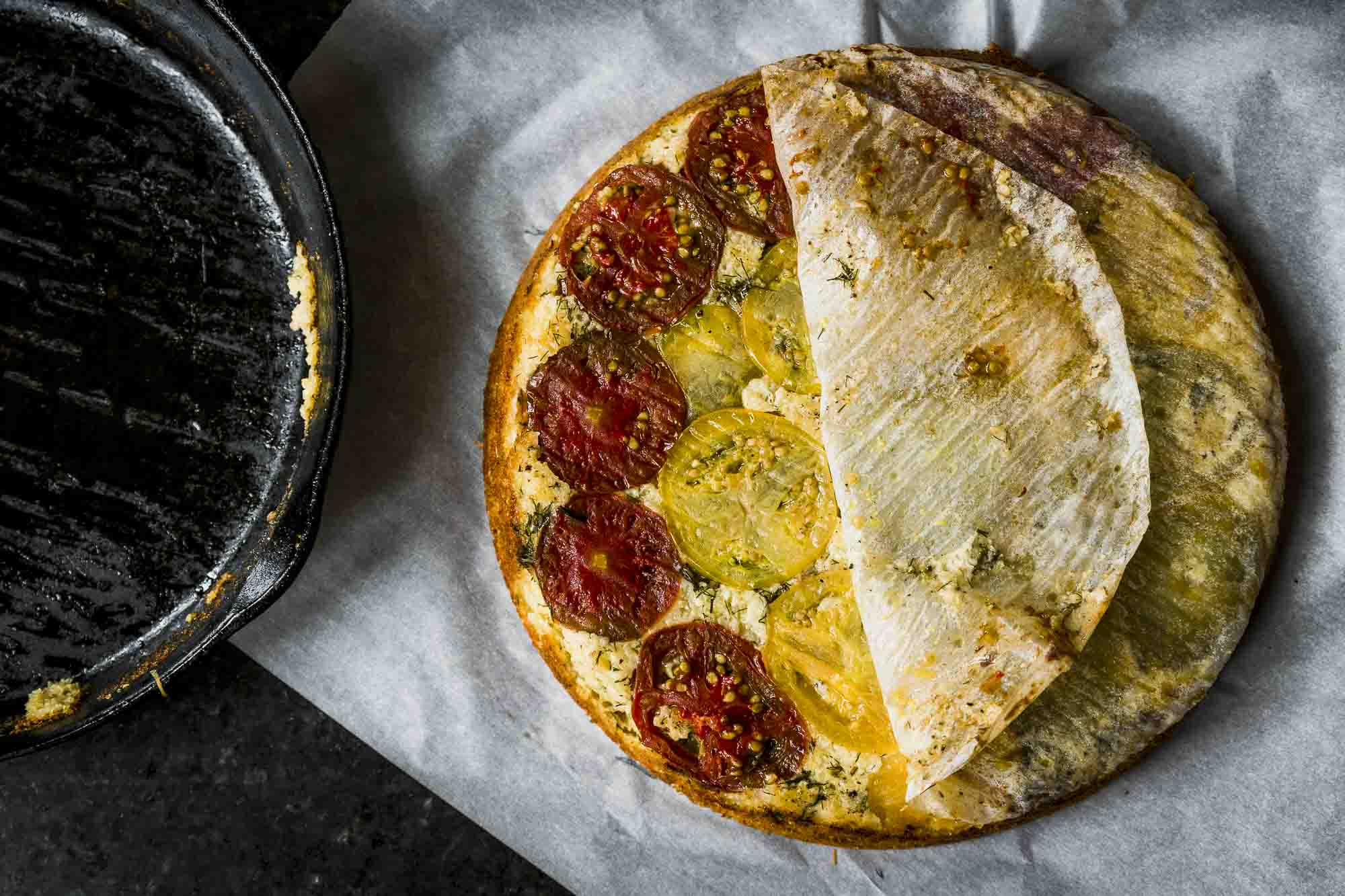 removing the parchment from the savory skillet cornbread: tomato upside down cake