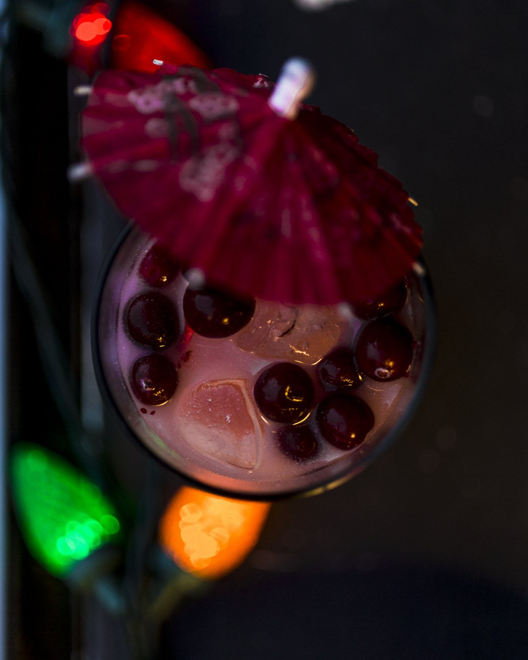 cranberry rum eggnog fizz cocktail with holiday lights