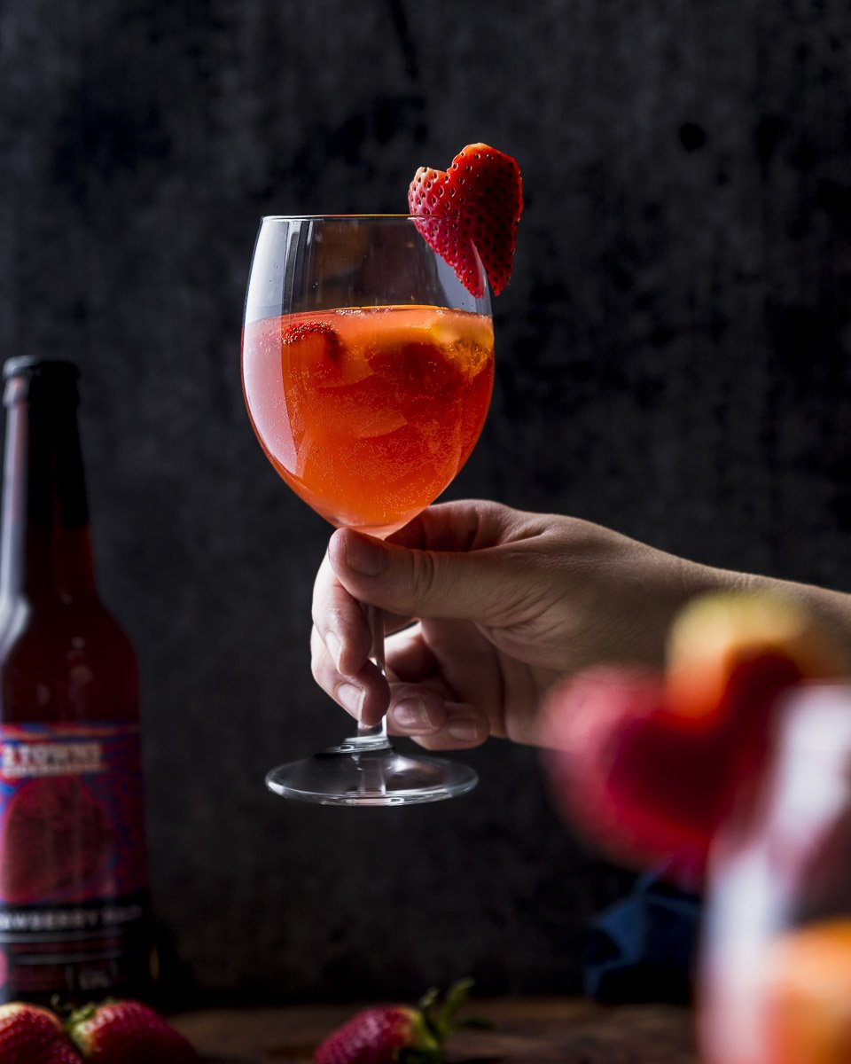 a hand holding a glass of strawberry hard cider sangria with heart shaped strawberry garnish