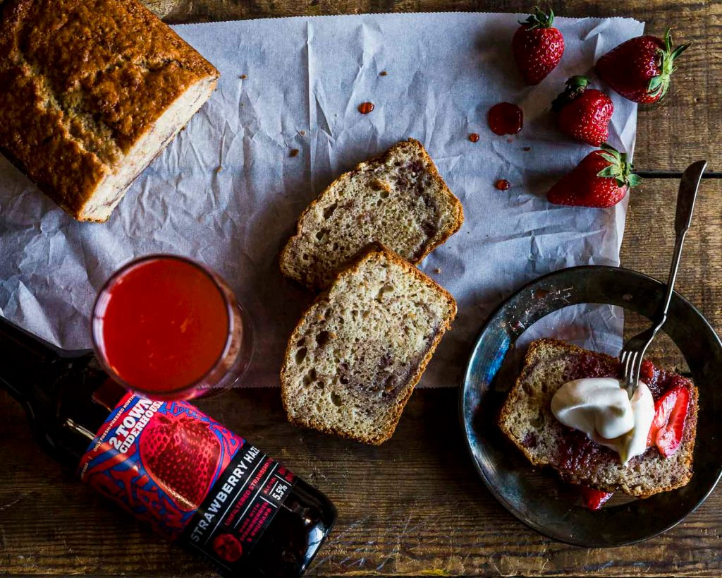 overhead shot of strawberry haze cider next to the Strawberry Cider Quick Bread w/ fresh strawberries and balsamic