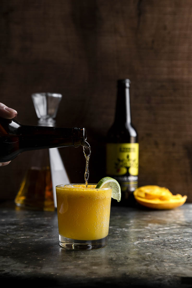 hard ginger cider and mango cocktail being poured