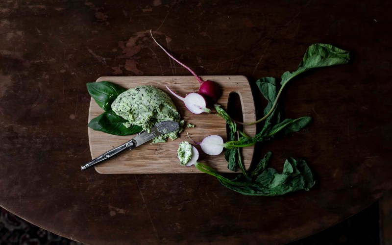 an overhead shot of a cutting board with fresh garden radishes topped with basil pesto butter