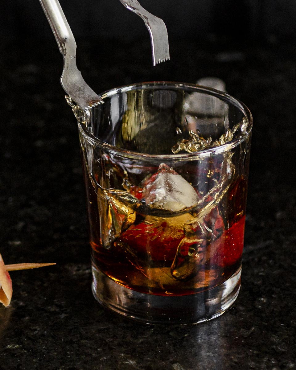 a splash shot of an ice cube falling into the glass of vermouth and gin