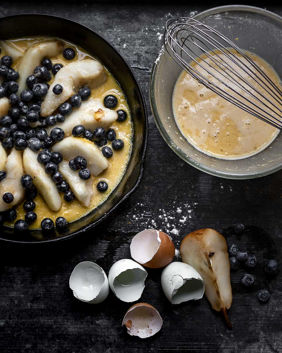 pear blueberry clafoutis with the first half of the batter set and the fruit added with the rest of the batter ready to be poured on top