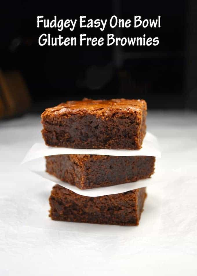 Three Gluten Free Brownies stacked together with baking paper between each slice.