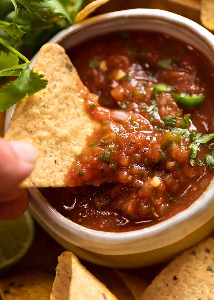 Close up of corn chip scooping up homemade salsa (Salsa recipe - restaurant style)