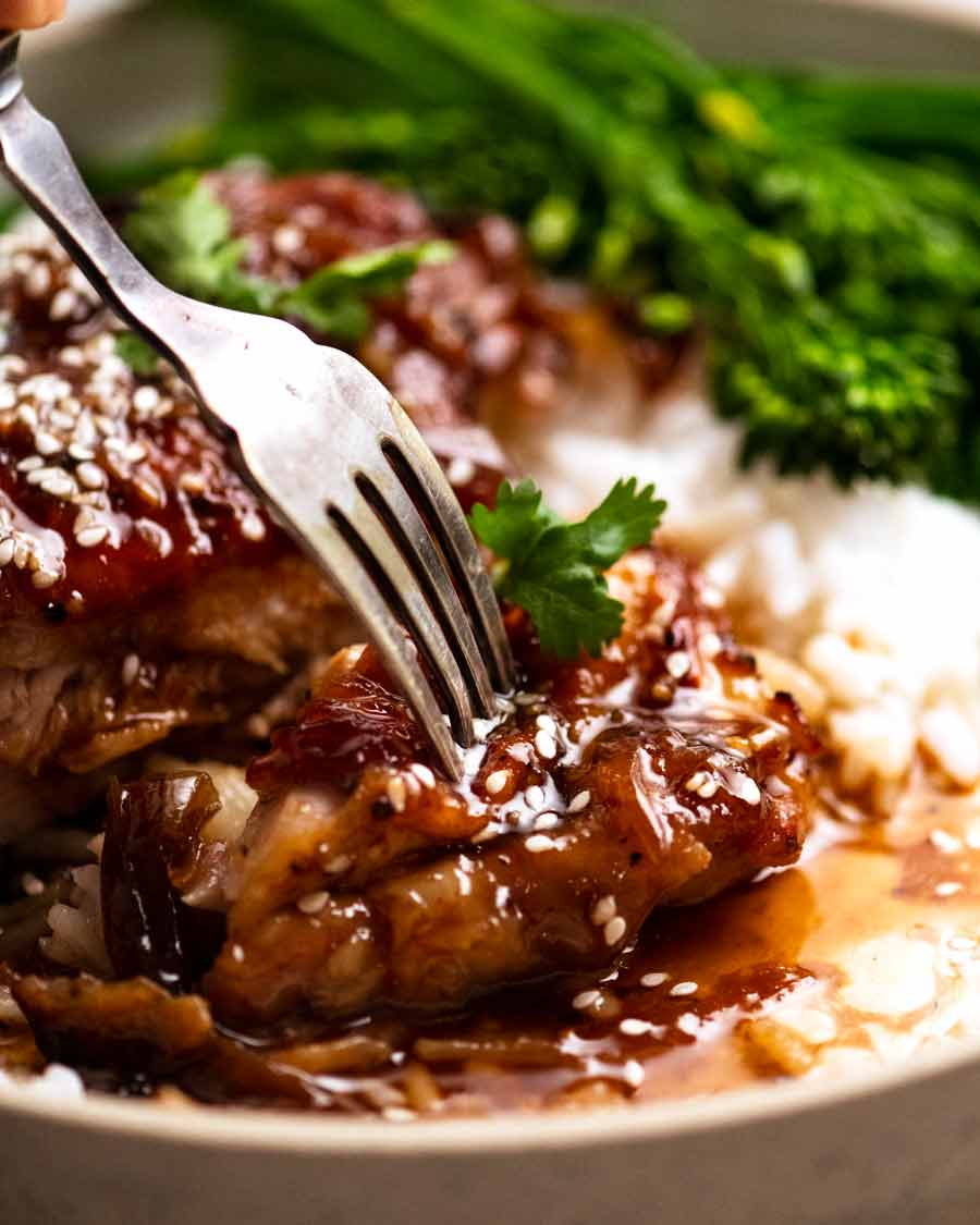 Fork picking up piece of Honey Soy Baked Chicken set on rice