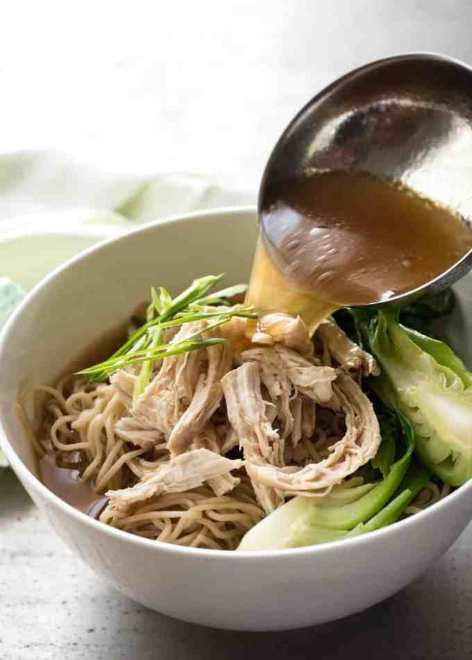 Chinese Noodle Soup broth being pour into a bowl over noodles.