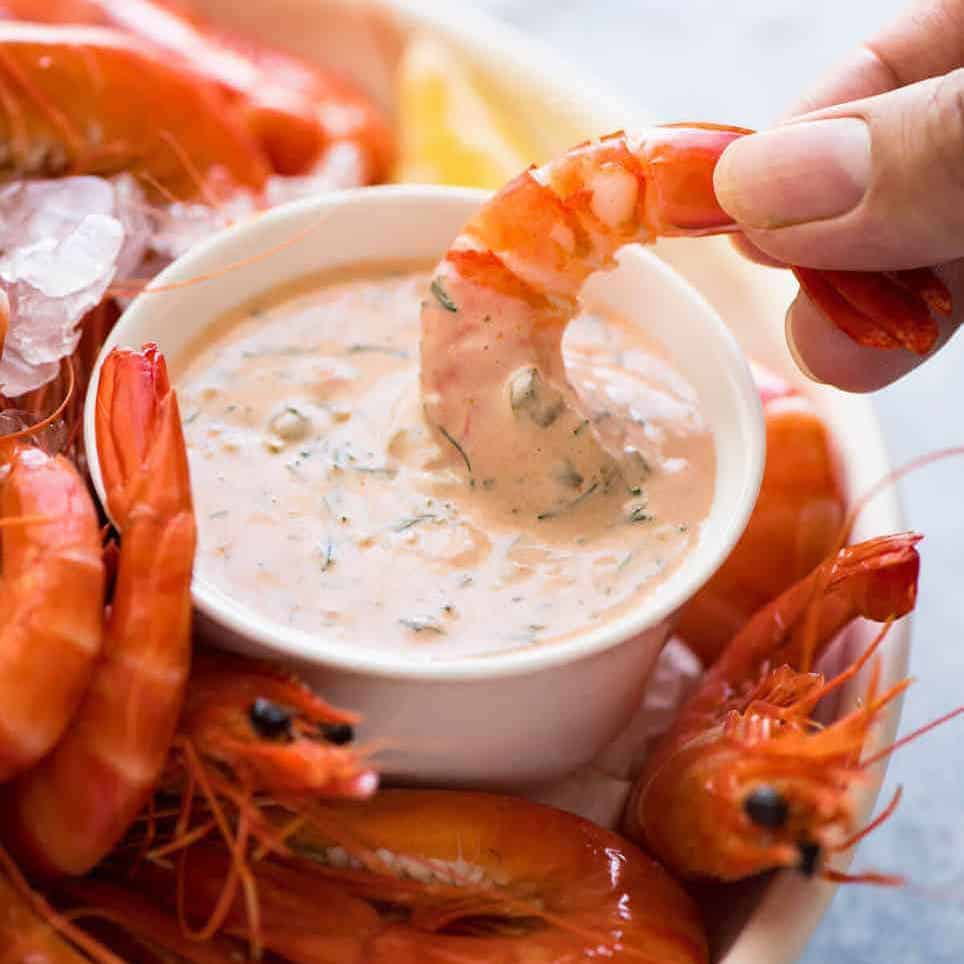 Prawn being dipped into Seafood Sauce