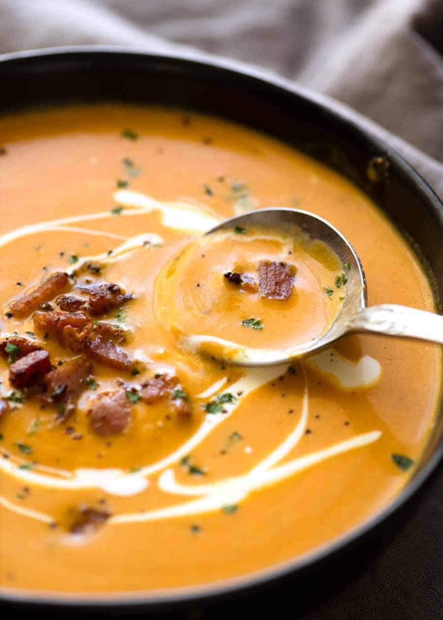 Close up of Carrot Soup in a rustic black bowl being scooped up with a spoon.