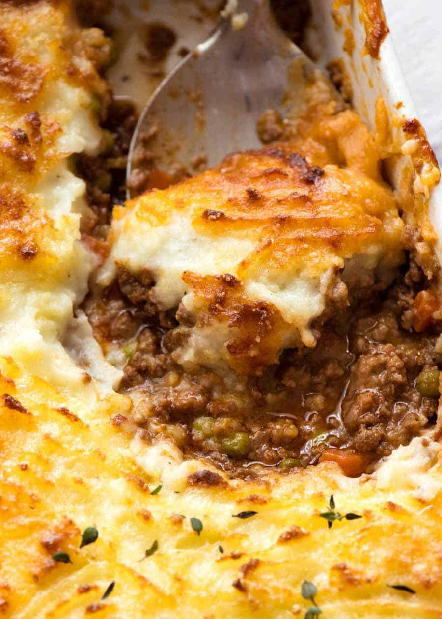 Close up of spoon scooping Shepherd's Pie out of a white baking dish, fresh out of the oven