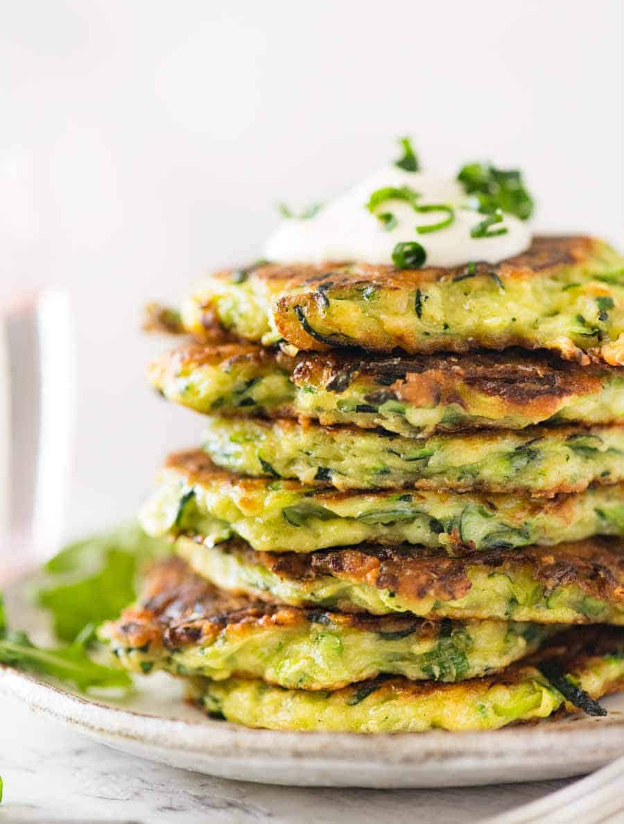Stack of Crispy Zucchini Fritters with a dollop of sour cream on a rustic brown plate with a side of arugula salad,