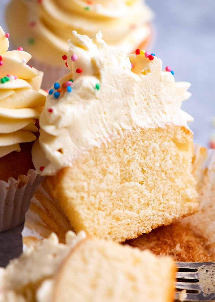 Showing the inside of moist Vanilla cupcakes with vanilla cupcake frosting
