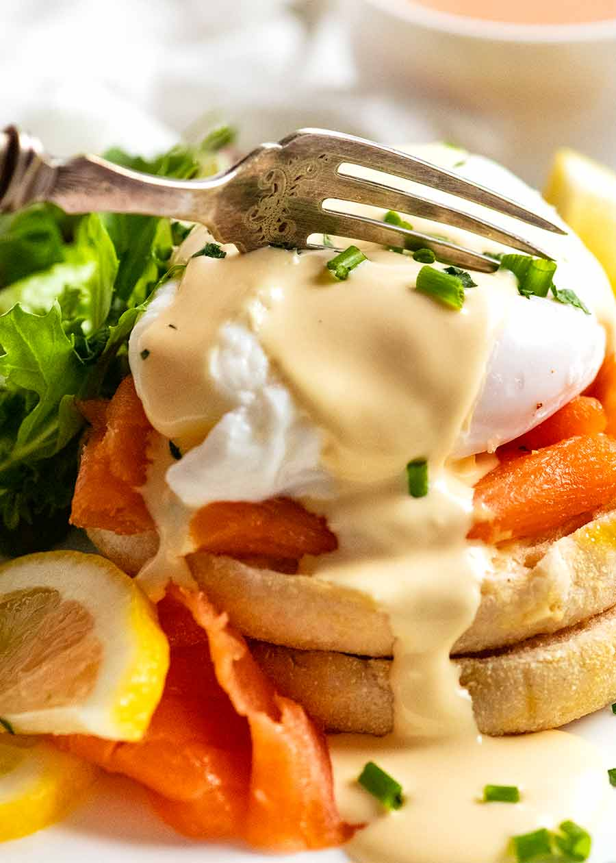 Fork cutting into Eggs Benedict with smoked salmon