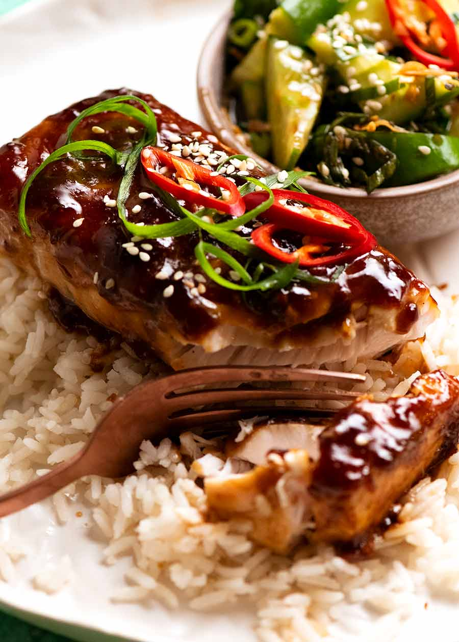 Close up of Asian Glazed Baked Barramundi on coconut rice with a side of cucumber salad