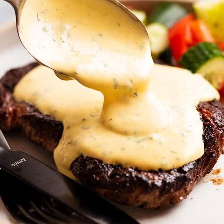 Spooning Bearnaise Sauce over steak