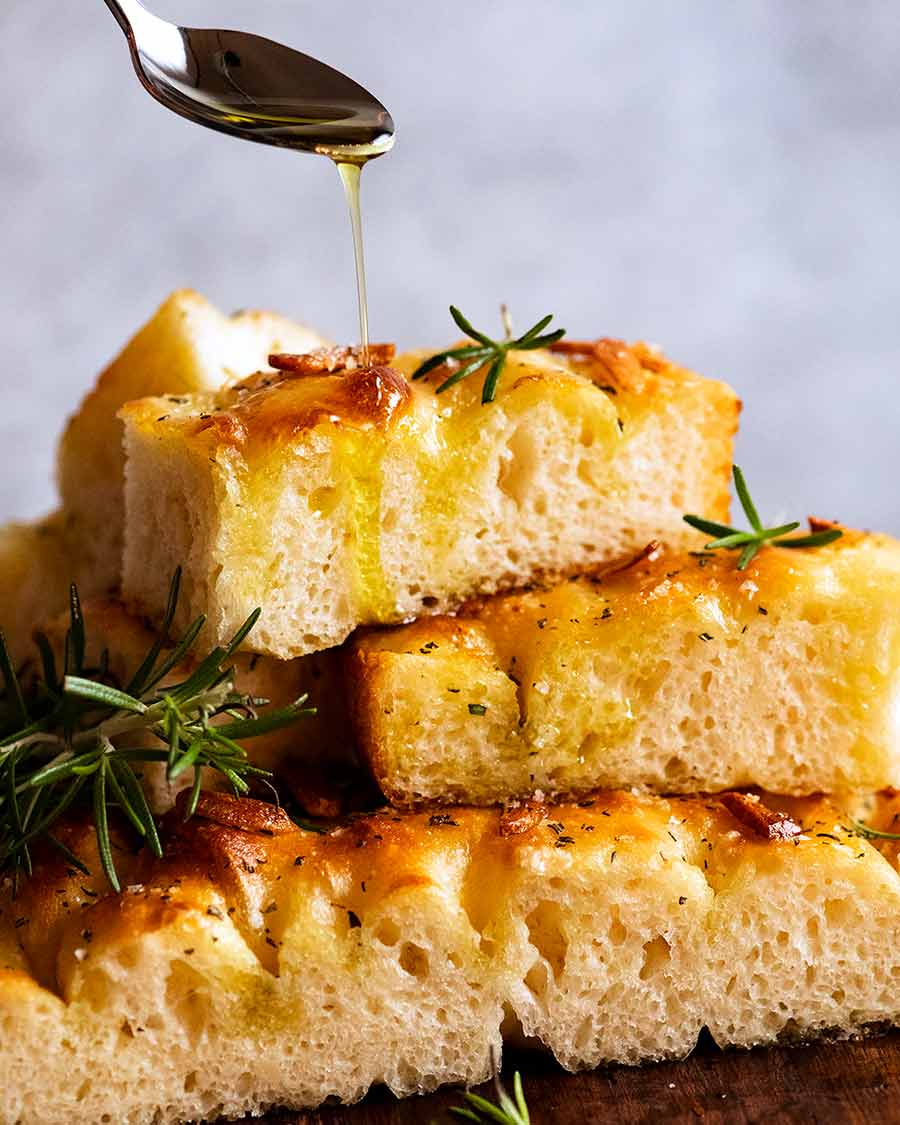 Drizzling a pile of warm focaccia with extra virgin olive oil