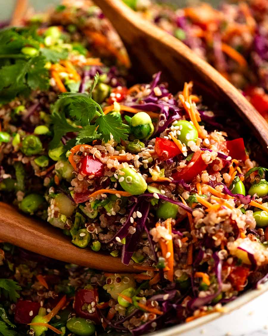Close up of wooden spoons scooping up Quinoa Salad