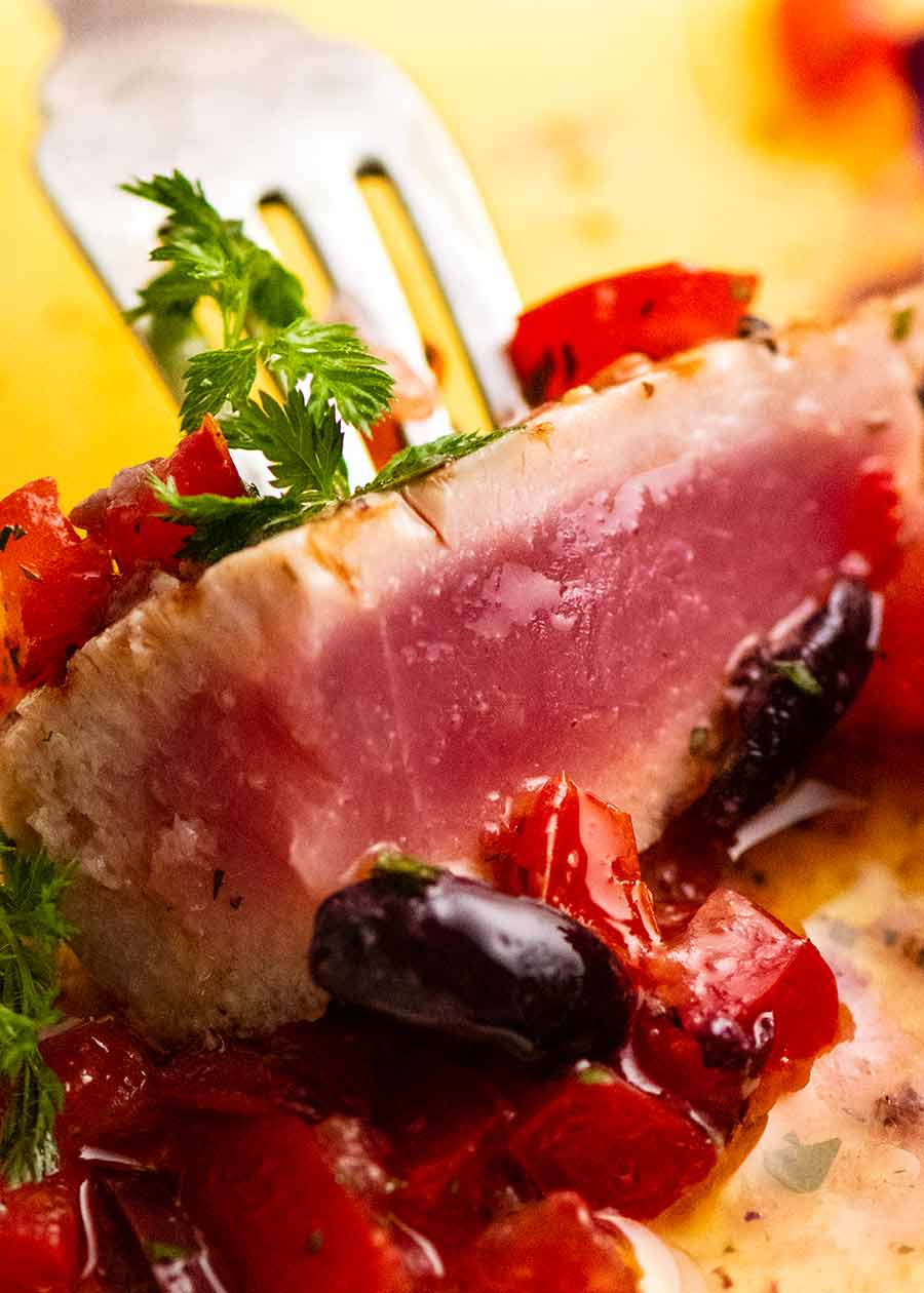 Close up of fork picking up a piece of Tuna Steak with Sauce Vierge