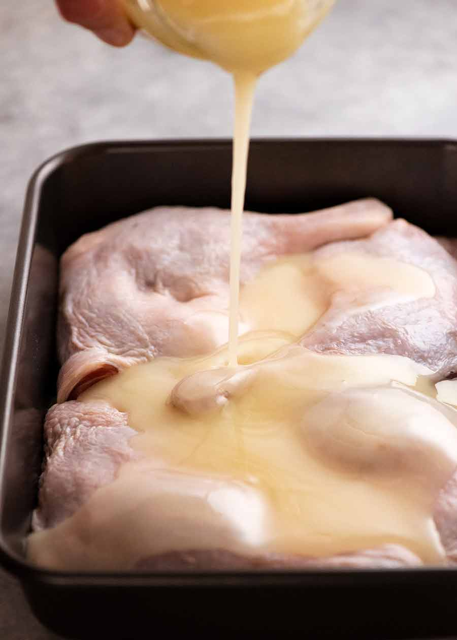 Pouring duck fat over duck legs to make Duck Confit