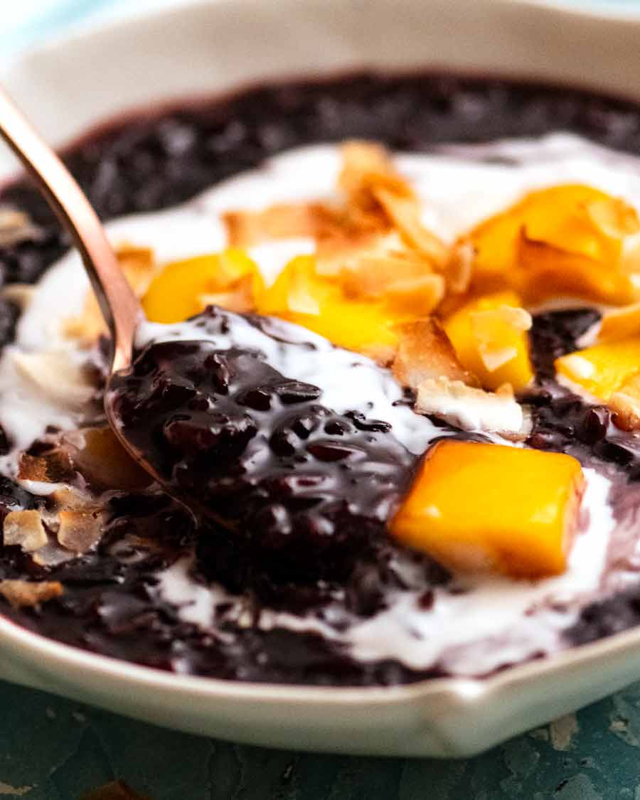 Close up of spoon scooping up Thai Black Sticky Rice Pudding