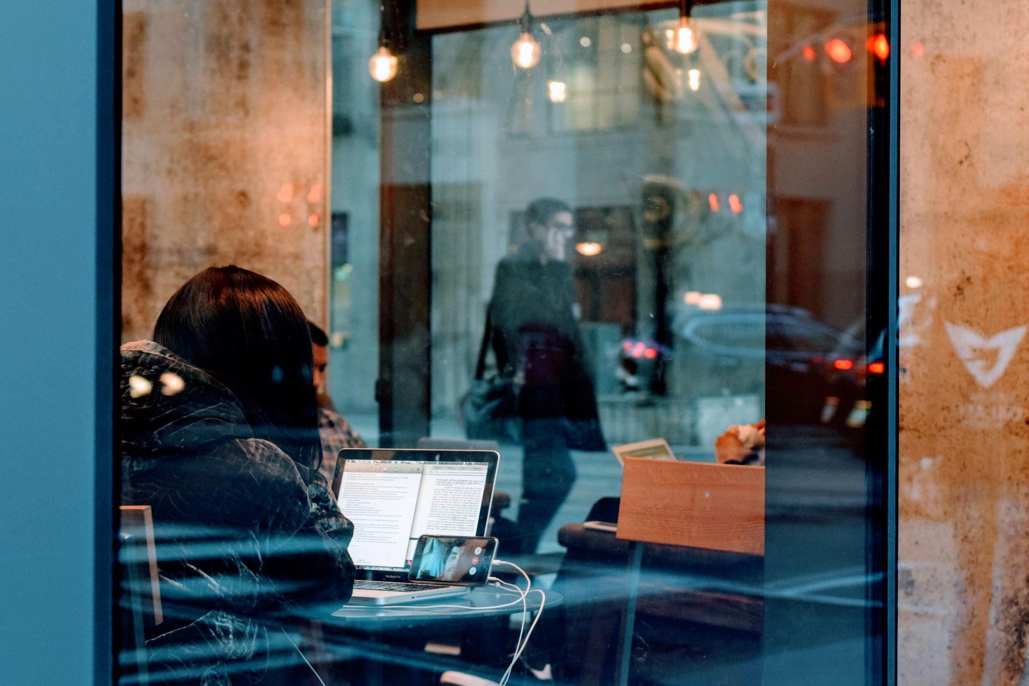 persona en un bar con su ordenador haciendo una reclamación laboral