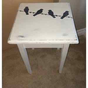 rustic table painted with four birds on a wire