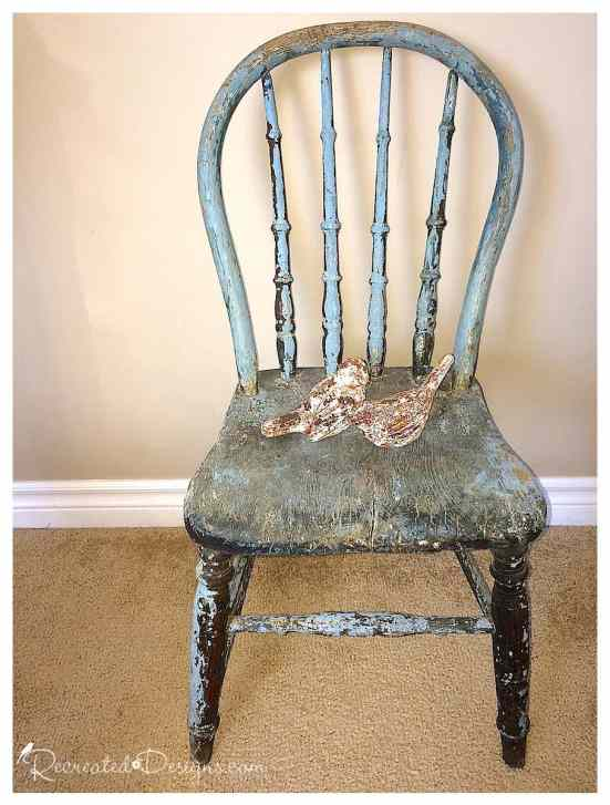antique chair covered in chippy blue paint