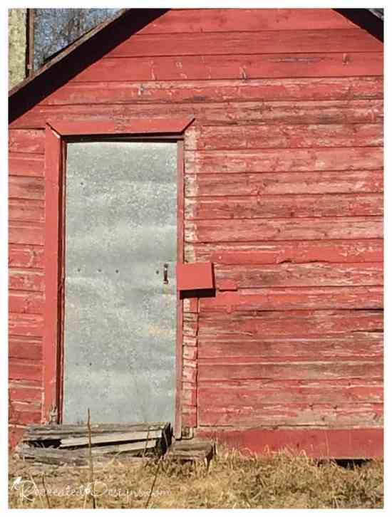 metal door with a small wood building painted with red chippy paint