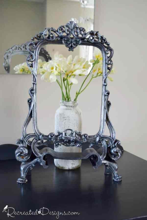 metallic black frame with jar of white flowers behind it