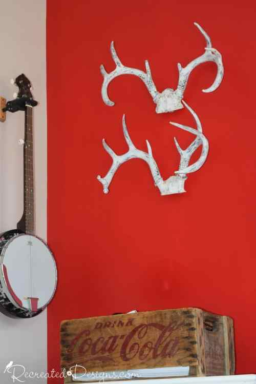 antlers on a wall with an old Coca Cola crate and a banjo