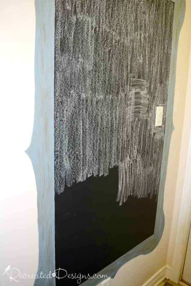 seasoning a newly painted chalkboard on a wall