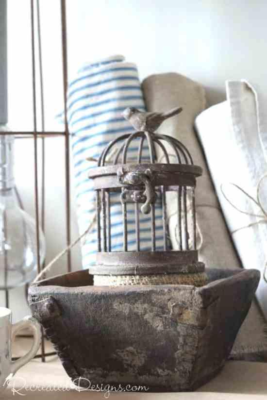 an antique berry bowl with a wrough iron bird cage